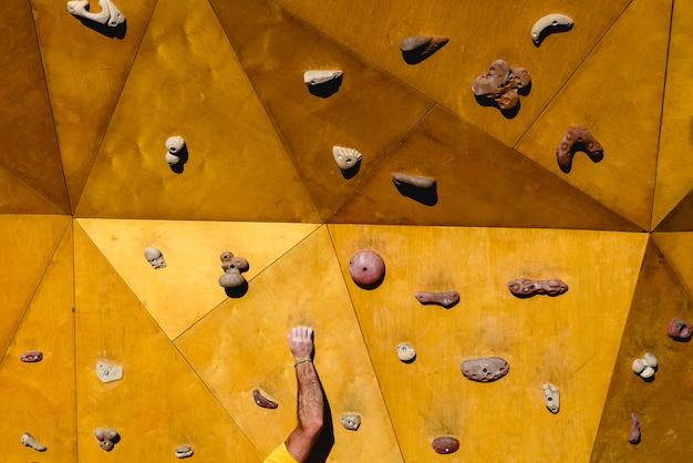 クライミングウォールのピストを登ろうとしている人の手