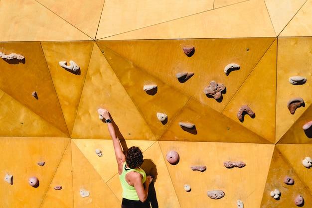 屋外で運動をしている良い形で強い女性と壁を登る