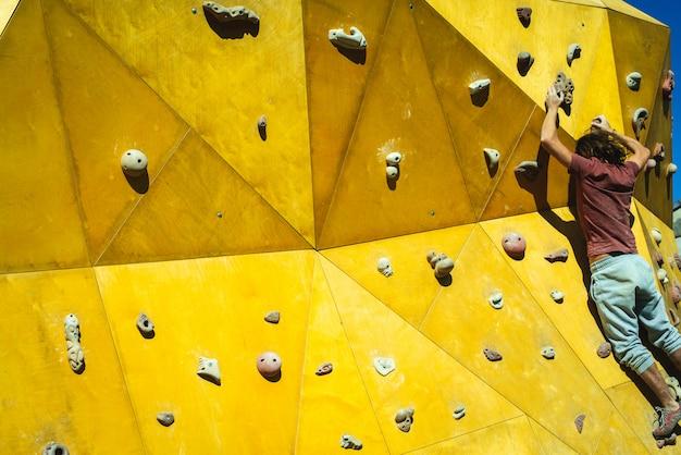 Спортсмен человек пытается достичь вершины скалодром с силой его руки и ноги.