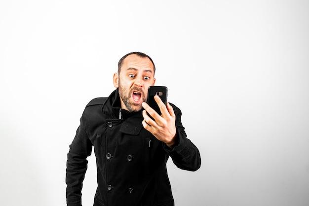 オーバーコートを持つ中年の男は白で隔離され、彼の携帯電話に腹を立てて叫ぶ。