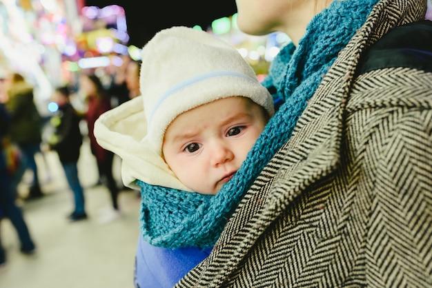 赤ちゃんが母親のカンガルースカーフを持ち込みます。