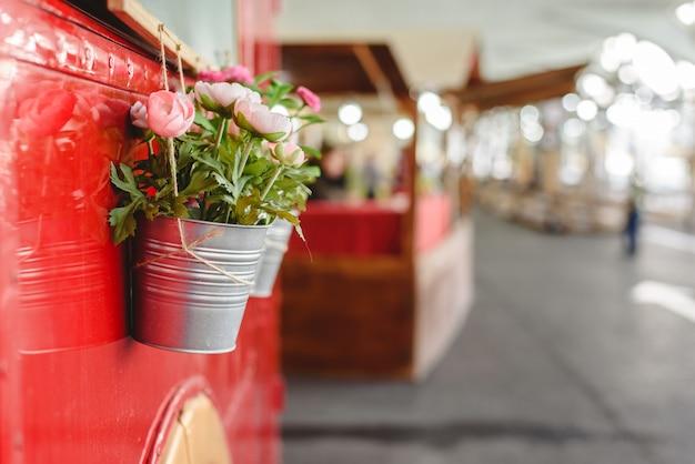 Горшки с декоративных растений, висит от красного автобуса на выставке старинных автомобилей.