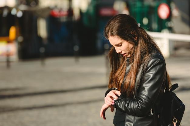 若い女性は通りで待っている間、約束に遅れて到着します。