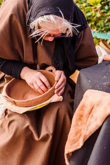 職人は中世の時代に偽装して、祭りの展示会で古い工芸品を見せました。
