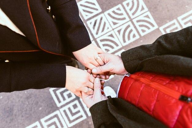 男性と女性が手を繋いでいる、彼女は宝石用原石の婚約指輪を着ています。