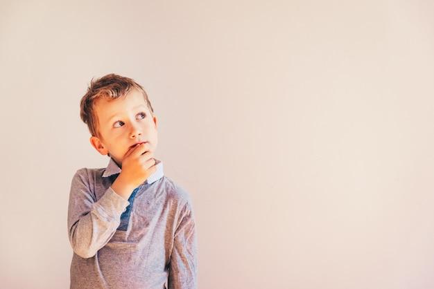 エリアコピースペースの白い背景の上の彼のアイデアについての疑問を持つ思いやりのある少年。