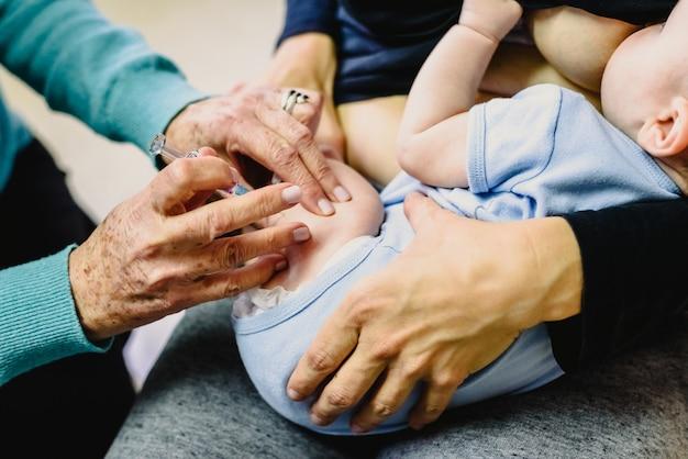 病気の拡大を避けるために、本物の赤ちゃんが小児科医によって大腿部に注射器で予防接種を受けています。