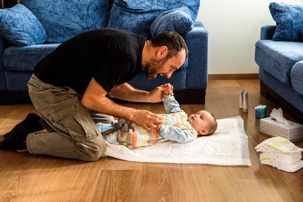 彼の家の居間で彼女と遊んでいる間彼の離婚後の独身の父親は彼の娘のおむつを変更する準備をした。