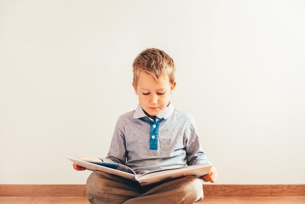 白い背景で隔離の彼の膝の上の本を読んで床に座っている少年。