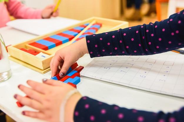 モンテッソーリ学校で木の材料を使用している学生少年の手。
