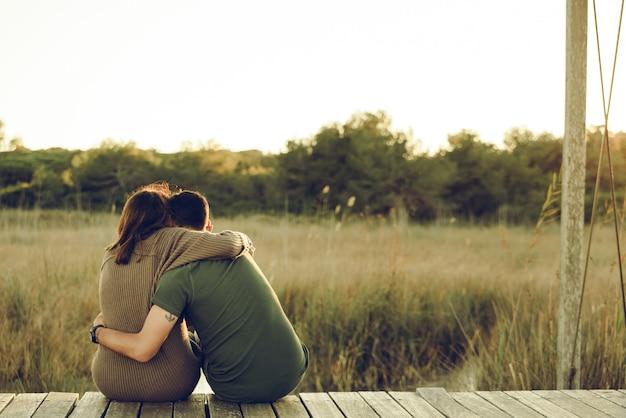 Влюбленная пара обнялась за спиной, чтобы примирить и отпраздновать свою любовь, сидя на природе.