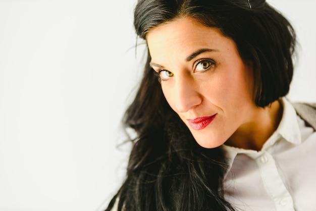 カメラと白い背景を見てカジュアル、美しい目のスタジオでブルネットの女性の肖像画。