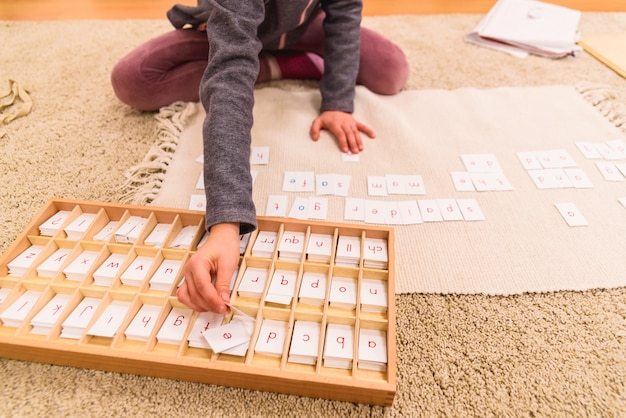 Студент девушка рука, используя карты с буквами, чтобы составить слова, сидя на полу классе своей школы монтессори.