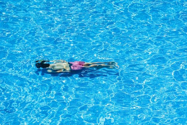 夏にプールでダイビングする子供たち
