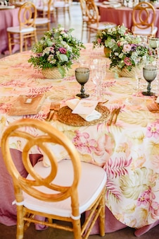 エレガントなカトラリーとビンテージスタイルのセンターピースのあるウェディングレストランのテーブルのためのフラワーアレンジメント。