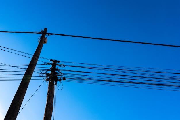 Поляки с кабелями электричества и телекоммуникаций увиденных снизу против предпосылки голубого неба.