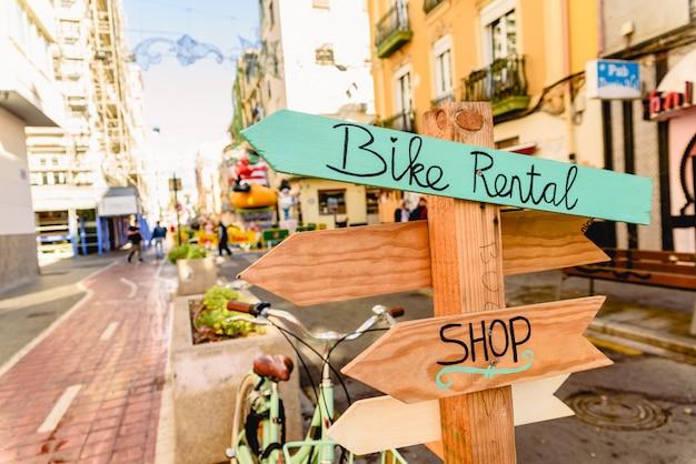 自転車レンタル店の道標としての木製の矢。自転車レンタル店の道標としての木造の矢。