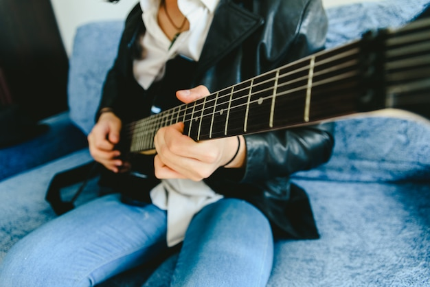 タッピングをしているコードを弾いているギターのマストのフレットにギタリストの指を置いた