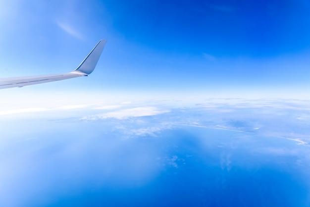 空の雲の上を飛行中に内側から見た飛行機の羽ばたき。