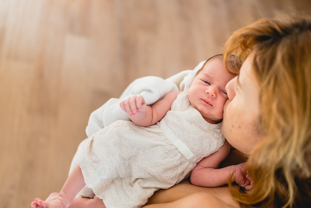 母は母乳育児の後彼女の生まれたばかりの娘にキス