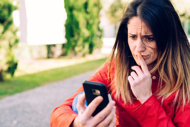 Молодая тысячелетняя студентка с грустным лицом, консультируясь со своим смартфоном