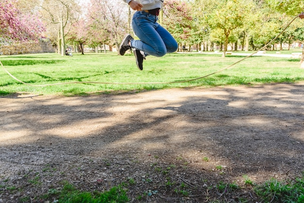Девушка играя скача веревку в парке в лете.
