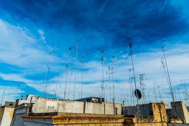 古いテレビアンテナでいっぱいの屋根があるバリの街の古い建物。