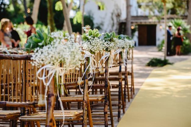 春の結婚式のための空の椅子のためのフラワーアレンジメント