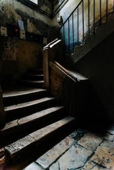 イタリア、バリの旧市街にある使われなくなった建物の暗いアトリウムにある古い石造りの階段。