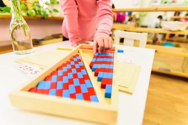 学校に追加することを学ぶために塗られた木の棒を使用して小さな女の子。