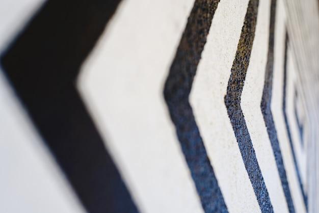 白い背景の黒い矢印のような線が方向を示す壁に描かれています。