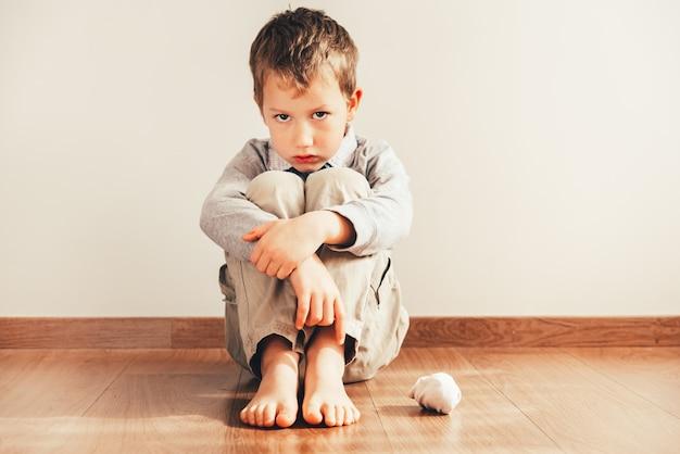 Ребенок сидит на полу босиком с грустным лицом за то, что не может надеть свою одежду.