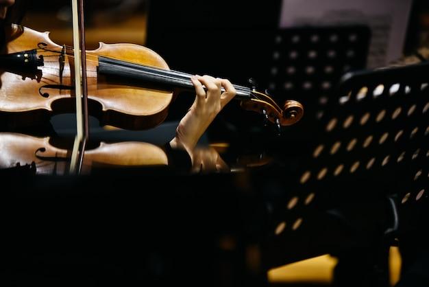 Скрипач во время концерта, предпосылка женщины в черноте.