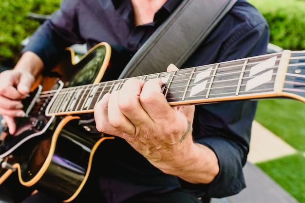 Гитарист играет на гитаре на открытом воздухе