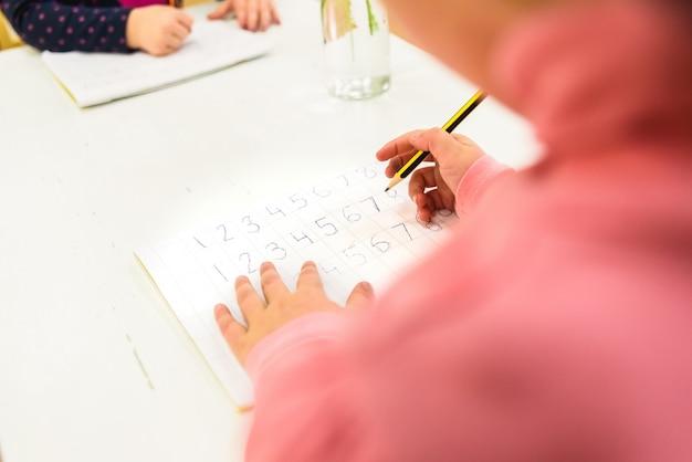 モンテッソーリ学校で識字の分野で書くことを学ぶ子供たち。
