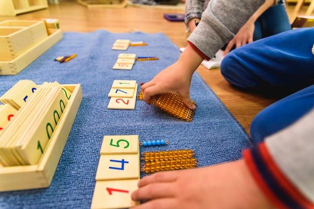 Руки мальчика студента используя деревянный материал в школе монтессори.