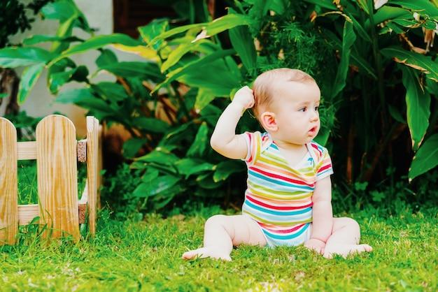 思慮深く頭をかいて草の上に座っている裸足の赤ちゃん。