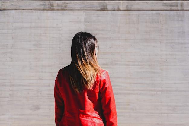 彼女の背中に落ち込んで悲しい態度でカジュアルなジャケットを着た女性。