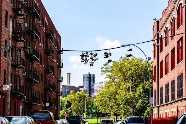 アメリカの都市の路上で通りから暴力団がぶら下がっているスニーカーのペア。