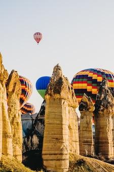 カッパドキアの上を飛んで、トゥルキアのスローガンと色とりどりの熱気球の詳細。