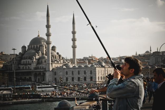 ガラタ橋の上の棒を持つトルコの漁師。
