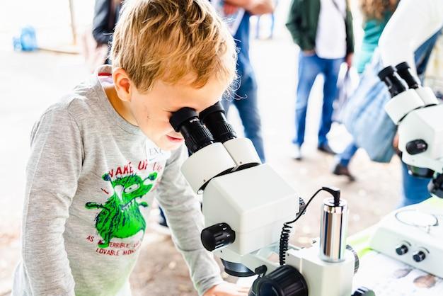 顕微鏡を通してバクテリアを見ている医学フェアの間に好奇心を持つ子供