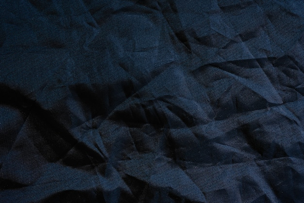 黒い背景のしわのあるプラスチック生地の質感のマクロ