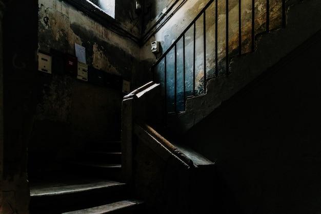 バーリの古い部分で使われなくなった建物の暗いアトリウムの古い石造りの階段
