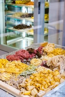 Много видов сырой итальянской пасты разных цветов и форм