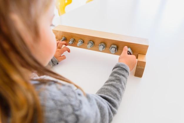 Девушка обрабатывает инструменты, чтобы затянуть гайки и болты.