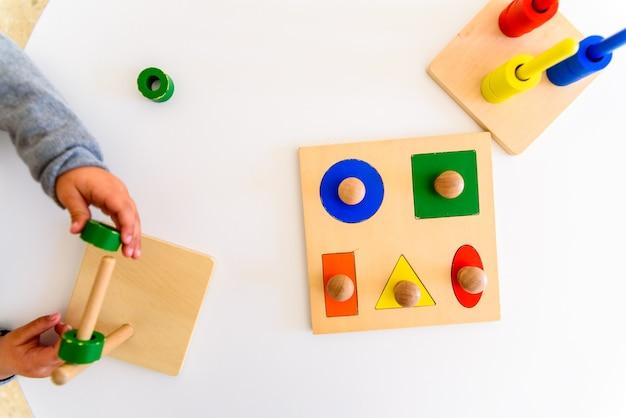 Девочка в школе развивает свои двигательные навыки в руках с использованием цветного древесного материала.