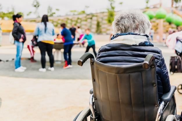 Пожилая женщина с ограниченными возможностями сидя спиной к спине в инвалидной коляске на игровой площадке.