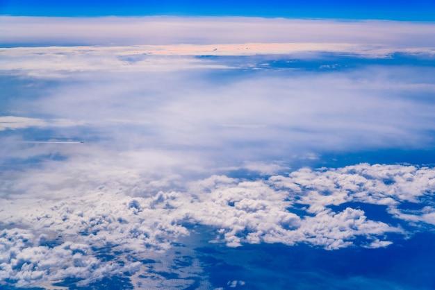 白い雲とそれを横切る飛行機と青空