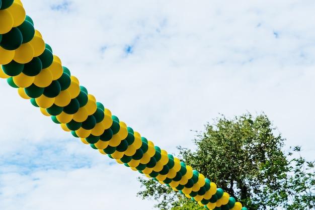 Фон с копией пространства многих раздутых воздушных шаров висит на синем небе